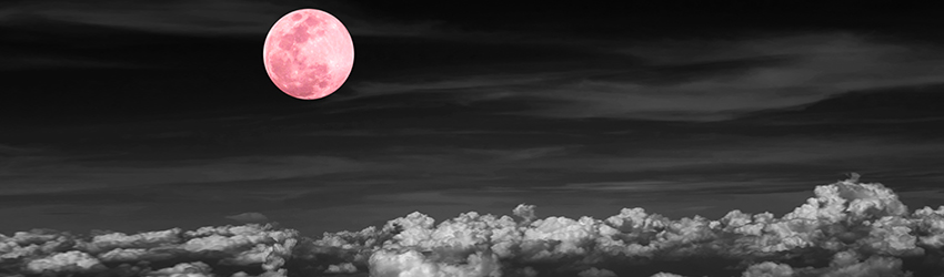A pink full moon in a black and white sky.