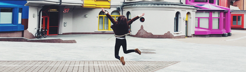 Person standing in the street jumping for joy.