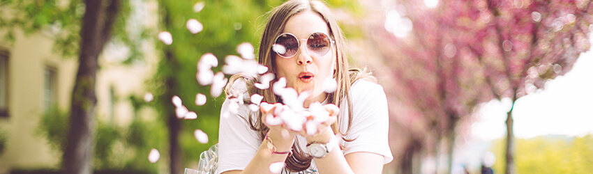 Person blowing flower pettles towards the camera during the spring equinox.