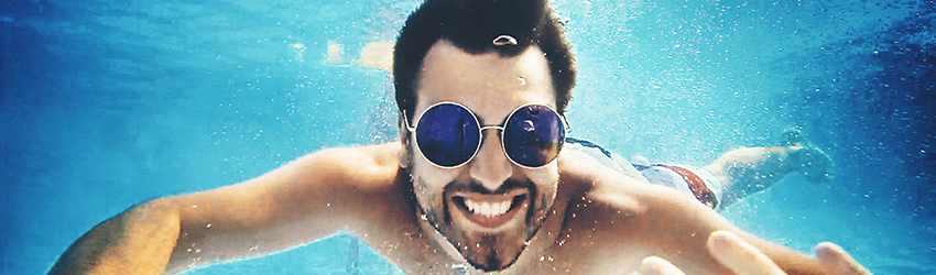 A Cancer man is swimming under water with sunglasses on.