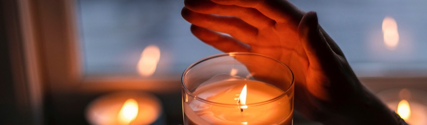A person holding a candle in a dark room in a dream.