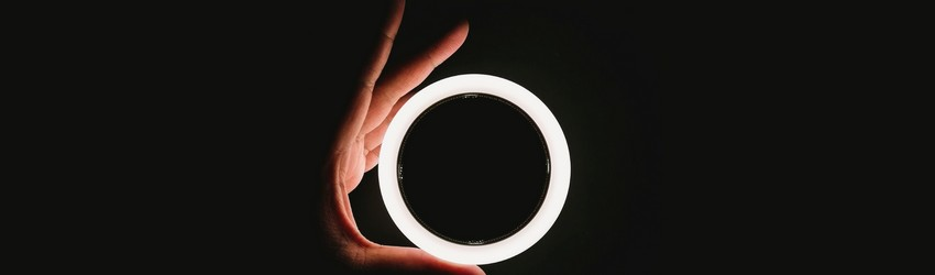A person is holding an LED light ring against a dark background in a dream-like state.