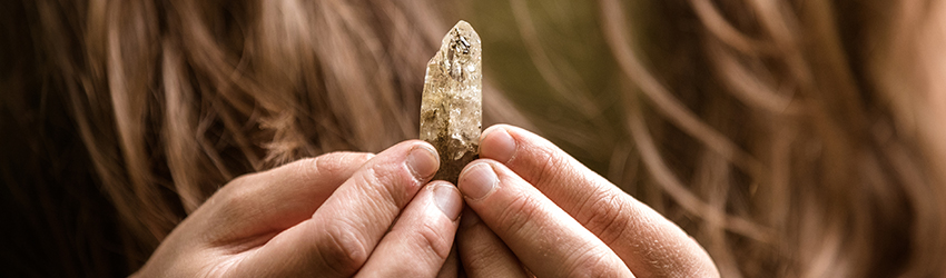 Woman holding a healing crystal in her hands.