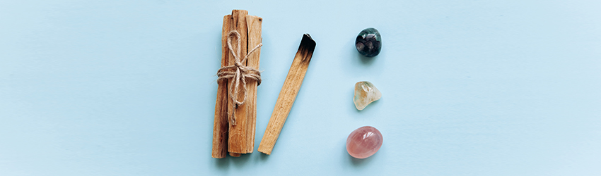 Some unburned sage sticks next to three crystals (one pink, one blue, one purple) on a powder blue background.