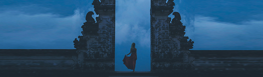 A shadowy figure in a billowy dress stands between two towers. The sky is a dark blue and it is becoming nightfall.