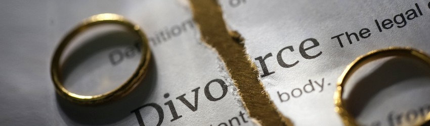 Two wedding rings sit on some legal papers that read