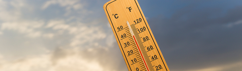 A thermometer in front of the sky.