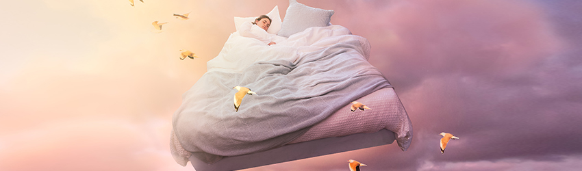 A woman is sleeping while her bed is flying through the air. She is surrounded by birds.