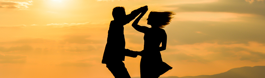 Two silhouetted people dance together in front of an orange sunset sky.