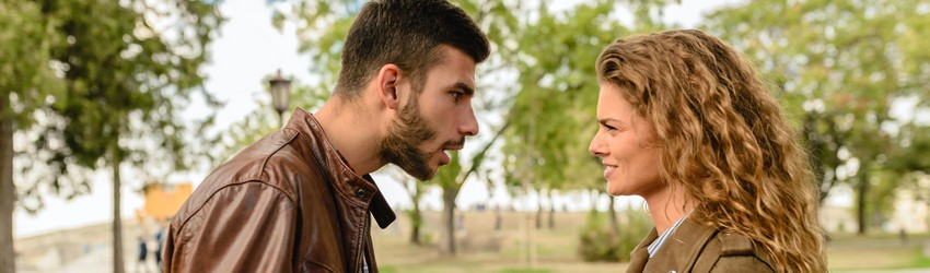 A man and a woman fight angrily in a park.