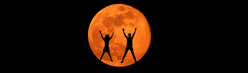Two silhouetted people jump in front of a red full moon in Aries.
