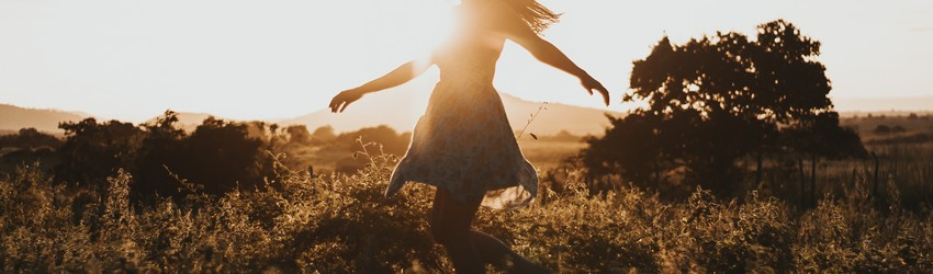 girl-running-in-field-with-sunset