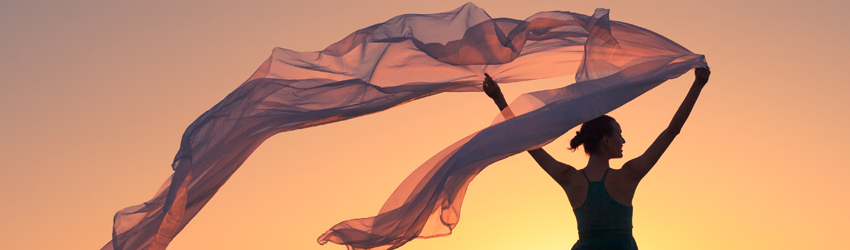 Person standing in the wind with a scarf blowing behind them. Reminiscent of a goddess.