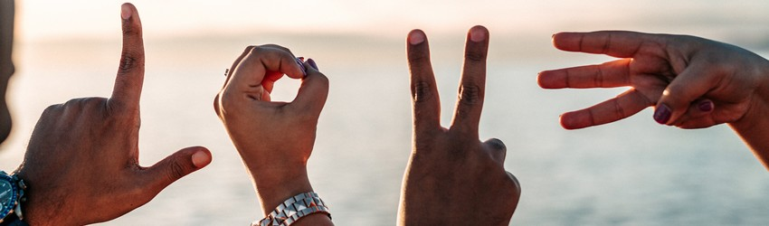People hold their hands up to spell LOVE with their fingers on a beach at sunset.
