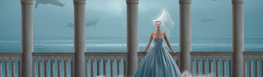 Woman wearing a water dress standing next to the ocean, whales swim behind her.