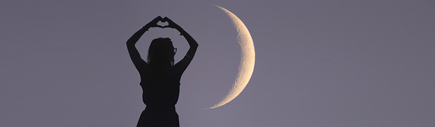 A woman holding a heart up in front of a full moon.