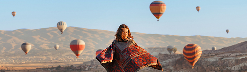 A tourist stands on a hill dancing in front of hundreds of hot air balloons rising like her intuition.