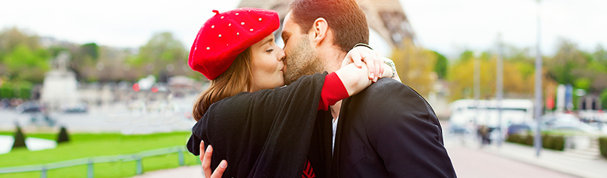 A couple kisses in front of the Eifel Tower in Paris.