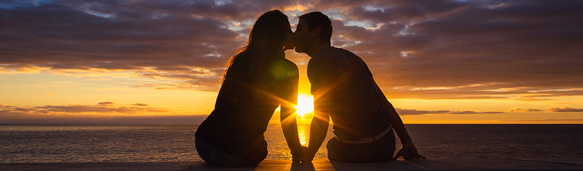 Two silhouetted people kiss in front of a sunset.