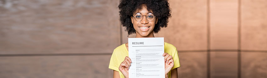A woman holding her resume in front of her.