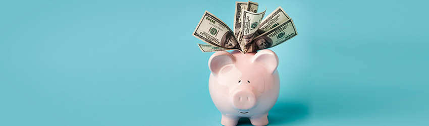 A piggy bank that is overflowing with cash.