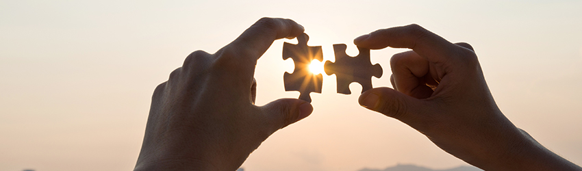 A person putting two puzzle pieces together in front of a sunset.