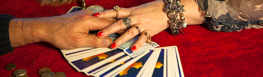Two people hold hands across a table. They are exchanging money for a tarot reading.