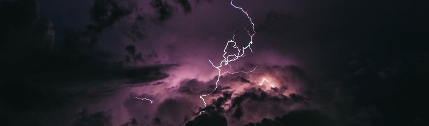 Lightning flashes purple in the distance.