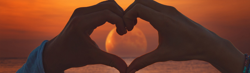 Two hands making a heart in front of the sunset.