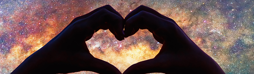 Two hands make a heart in front of a galaxy image.