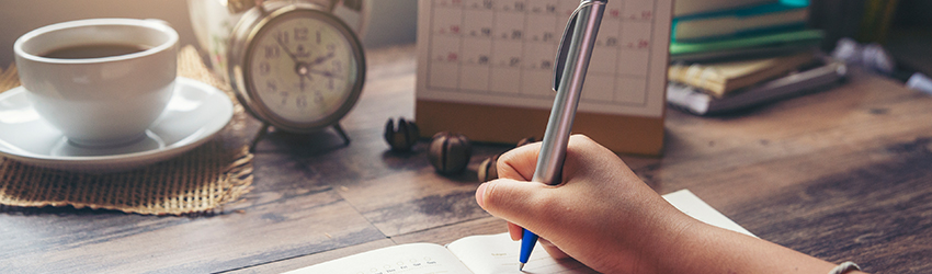 Person writing in their day planner while looking at a desk calendar.