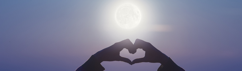 A woman holds her hands up in front of the Full Moon in a heart shape.