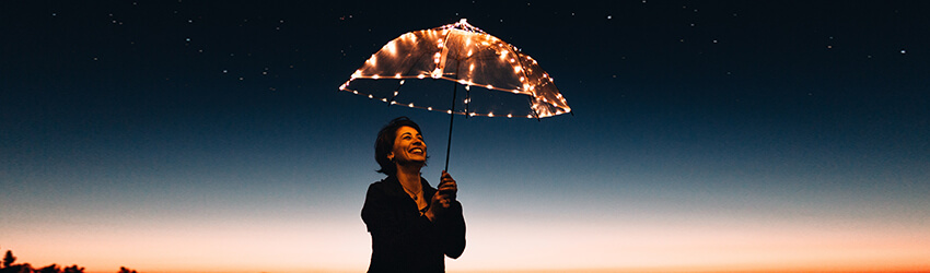 Woman standing outside during spring, she is holding an umbrella.