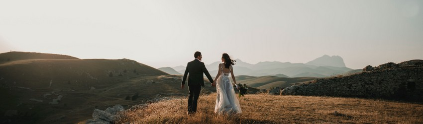 A man and woman take wedding photos in a field.