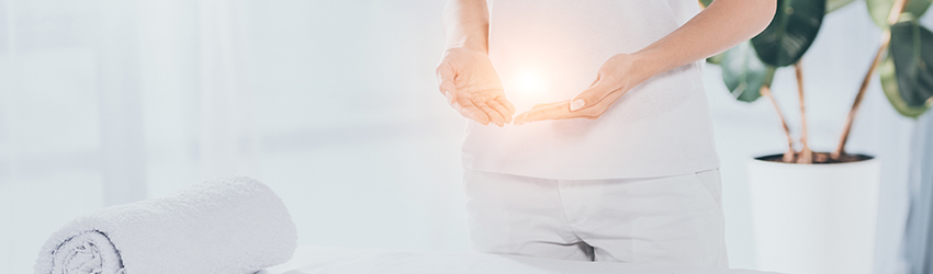 A person holds their hands open in front of their stomach. In it is a ball of light.
