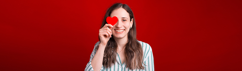 A woman with long red hair on a red background holding a red heart in front of her right eye. She is laughing.