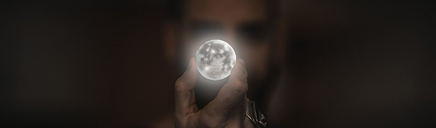 Person holding a full moon in front of their face.