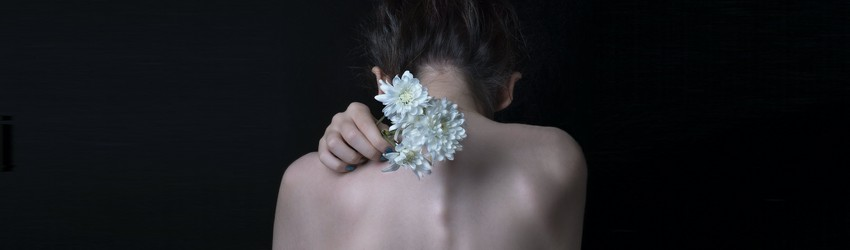 A shirtless person faces backwards with flowers behind their neck.