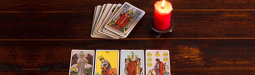A 4-card Tarot spread on a wooden table. The cards are lined up in front of the viewer with the rest of the deck in a pile above them.