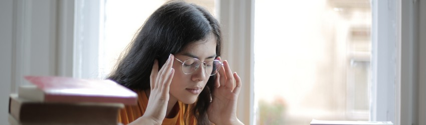 A person touches their forehead and temples because they have a painful headache.