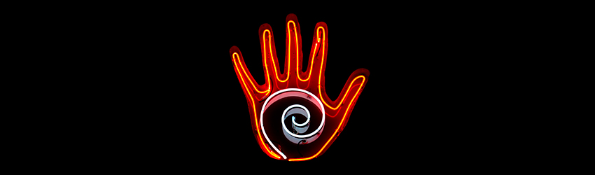 A neon palmistry sign. It has a red hand and a white swirl in the middle.