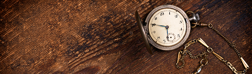 A pocketwatch on a wooden table.