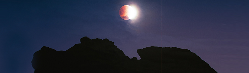A quarter moon displayed in a dark blue sky above the mountains.