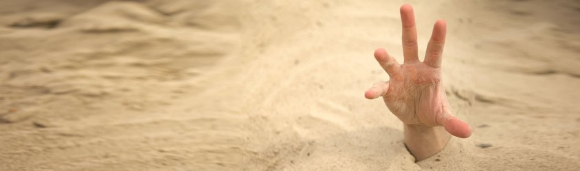 A person reaching their hand out of some quicksand.