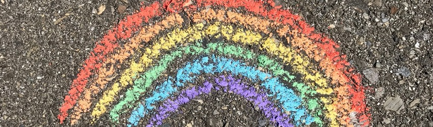 A chalk rainbow is drawn on the pavement.