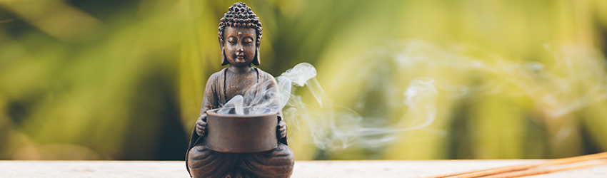 A buddha statue with incense inside.