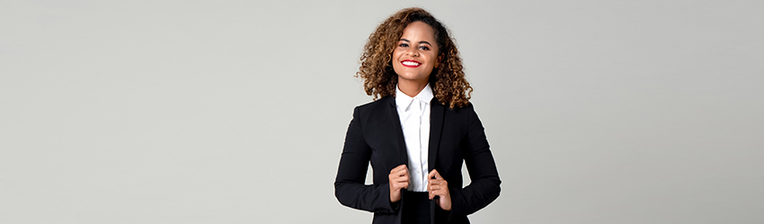 A woman in a business suit stands in front of white wall smiling.