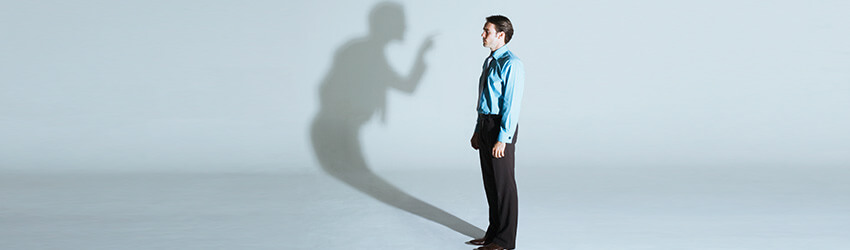 A man in a suit is being lectured by his shadow.