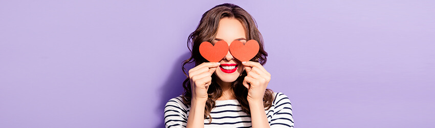A woman holding two heart shaped cut outs in front of her eyes.