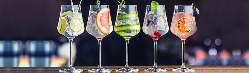 5 summer cocktails sit on a counter in wine glasses. Each has a different fruit in it.